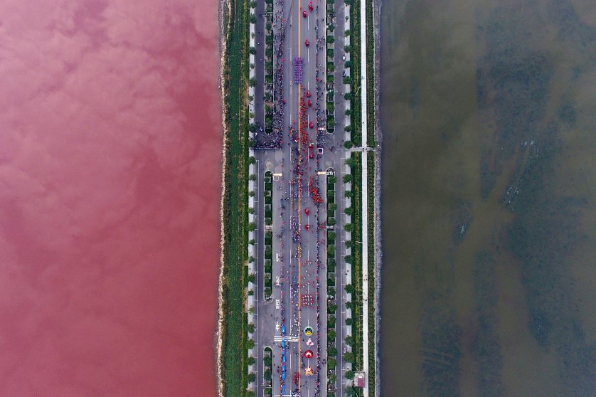 A salt lake which is separated by a road, shows parts of it in different colours due to algae, in Yuncheng, Shanxi Province, China