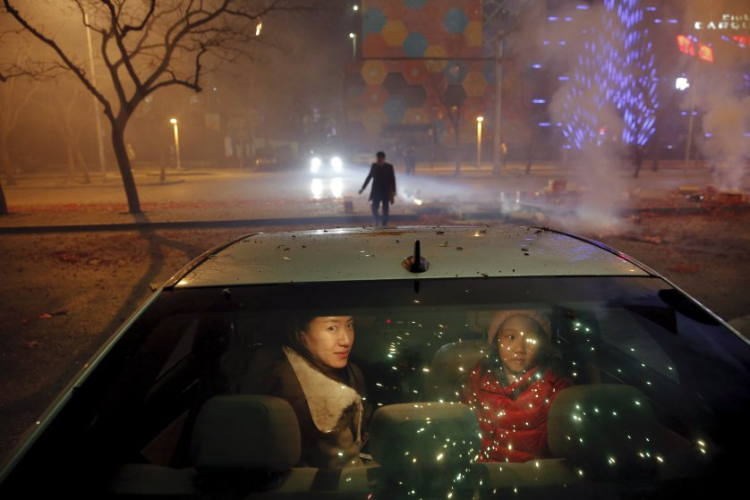 A girl and a woman sit inside the car as firecrackers and fireworks explode celebrating the start of the Chinese Lunar New Year of Monkey in Beijing