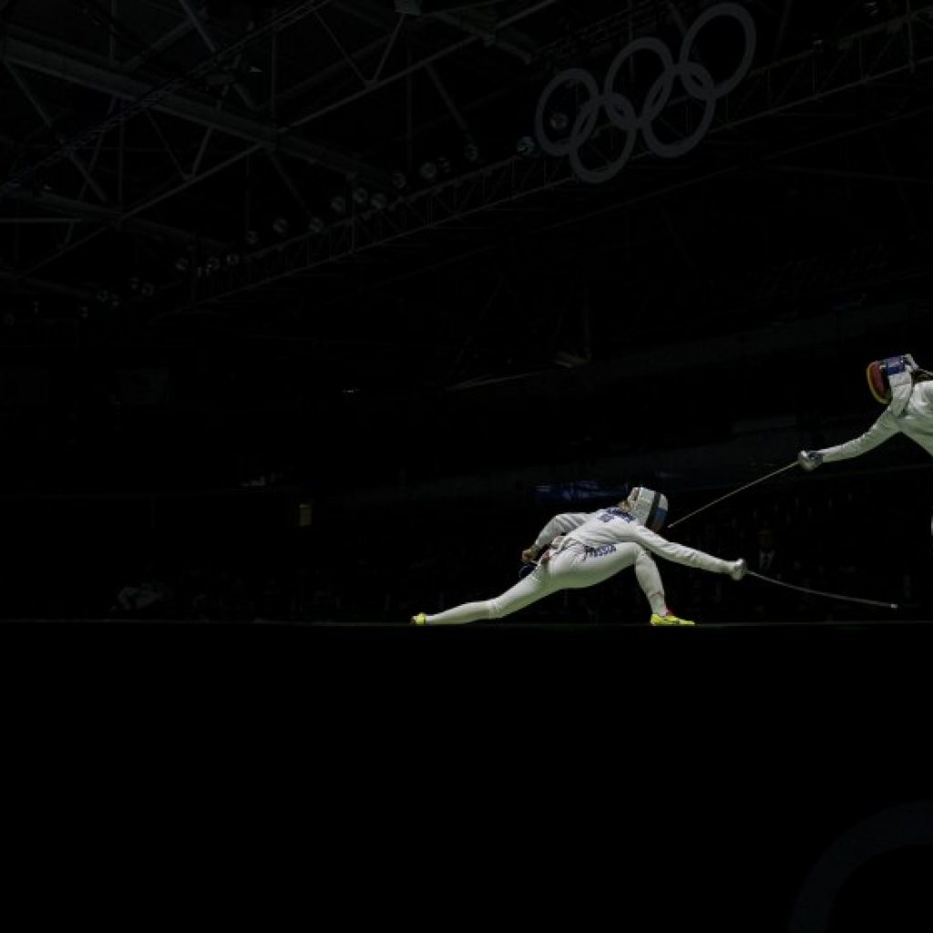 Violetta Kolobova of Russia, left, vies with Simona Pop of Romania in the women's epee team fencing semifinal at the Carioca Arena 3 during the 2016 Summer Olympics in Rio de Janeiro.