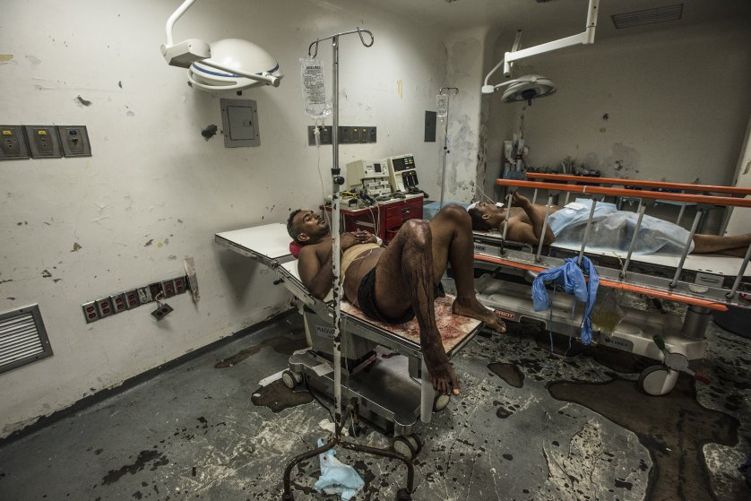 Jose Villarroel waits for hours in an emergency operating room at Luis Razetti Hospital.
