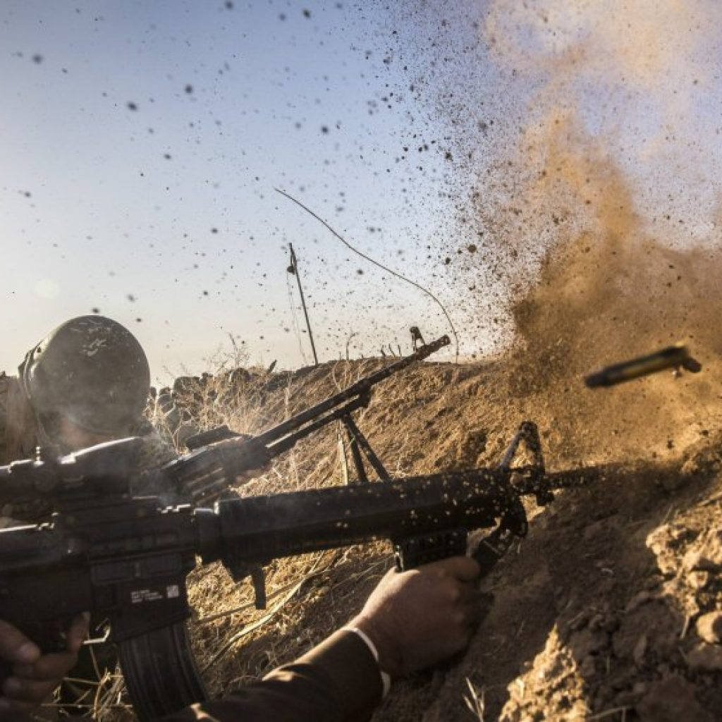 Kurdish pesh merga troops fire at Islamic State positions as they move toward the Iraqi town of Badana Pichwk on Monday morning.