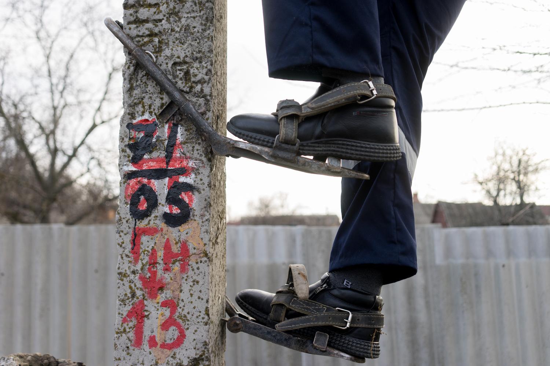 Алексей забирается на столб с помощью «когтей»