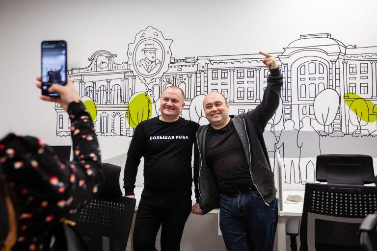 Александр Колб и экскурсовод Максим Розенфельд на фоне скетчей Олеси Корниловой